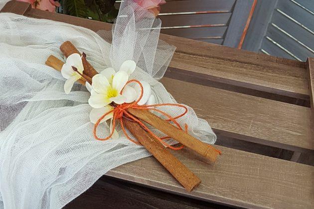 μπομονιέρα με ξύλα κανέλας, πορτοκαλί κορδόνι & λευκά λουλούδια
