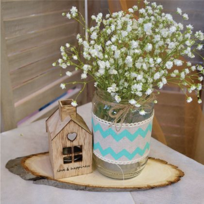 Center piece γιά βαπτιση με ξύλινο κορμό και πάνω DIY βαζάκι με διακόσμηση βεραμα΄ν ύφασμα και λευκή δαντέλα και επιπλέον διακόσμηση ένα ξύλινο σπιτάκι
