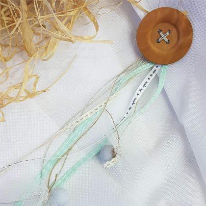 Κρεμαστή μπομπονιέρα βάπτισης με ξύλινον κουμπι και διάφορες κορδέλες