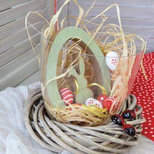 Πασχαλινά δώρα: σύνθεση με γυάλα, ξύλινο λαγό, στεφάνι μπαμπού και διακοσμητικά χρωματιστά αυγά.