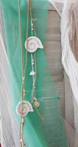 Γάμος με θαλασσινό θέμα, τυρκουάζ κρεμασμένη γάζα διακοσμημένη με πέτρινα διακοσμητικά κοχύλια