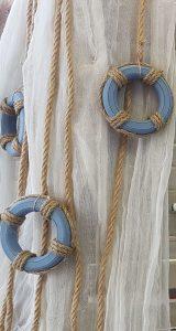 Γάμος με θαλασσινό θέμα, λευκή κρεμασμένη γάζα διακοσμημένη με σχοινιά και μπλε διακοσμητικά σωσίβια