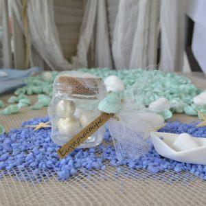 Μπομπονιέρες γάμου με θέμα θάλασσα: γυάλινο βαζάκι με κουφέτα, δεμένο με τούλι και στολισμένο με τυρκουάζ κοχύλι.
