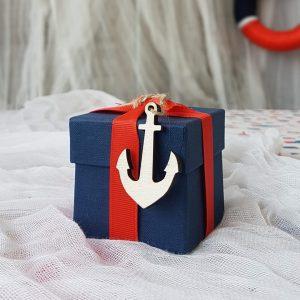 παιδικές μπομπονιέρεσ με σκούρο μπλε κουτί, κόκκινη κορδέλα και ξύλινη άγκυρα