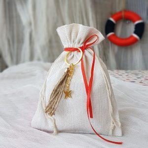παιδικες μπομπονιέρες πουγκί στο χρώμα της άμμου με διακοσμητικό αστερία μπρελόκ