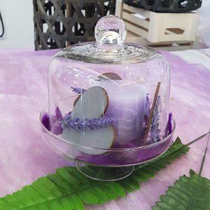 πρωτότυπος στολισμός γάμου, center piece με γυάλινη τουρτιέρα διακοσμημένη με λιλά κερί, ξλυλινη καρδιά και χρωματιστές πέτρες
