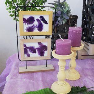 πρωτότυπος στολισμός γάμου, ξύλινη κορνίζα με πούπουλα και μπεζ κηροπήγια με μωβ κεριά