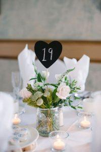 Μικρός μαυροπίνακας μέσα σε γυάλινο βάζο με λουλούδια