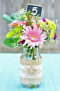 Διακοσμηση τραπεζιού για βαπτιση κοριτσιού με βάζο πολύχρωμα λουλούδια και μαυροπίνακα
