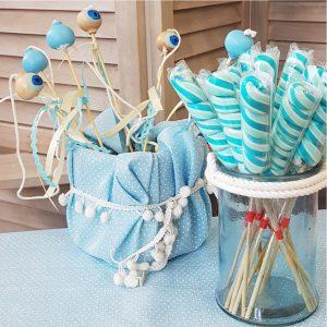 βάζο με γαλάζια γλυφιτζύρια και κουβαδάκι ντυμμένο με γαλάζιο ύφασμα και γεμισμένο με ξύλινα διακοσμητικά μάτια σε sticks