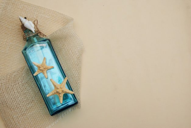 Γαλάζιο μπουκάλι με κολλημένα κοχύλια και φυσικό σχοινί