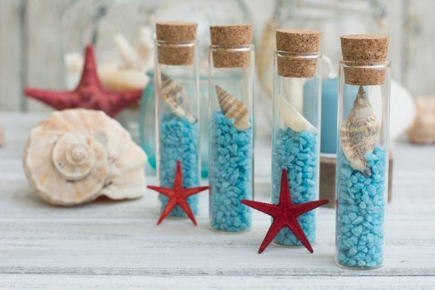Γυάλινοι δοκιμαστικοί σωλήνες με γαλάζια πετραδάκια, κοχύλια και αστερίες