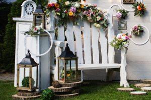 σύνθεση για διακόσμηση κήπου με ξυλινο λευκό παγκάκι, μεταλλικά φανάρια και φέτες κορμών δέντρων