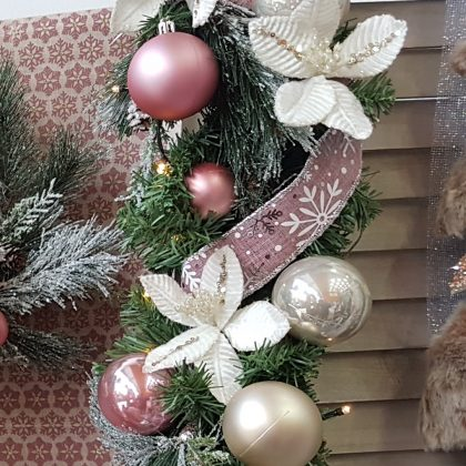 Χριστουγεννιάτικη σύνθεση με πράσινη γιρλάντα, ροζ και χρυσές μπάλες και λευκά λουλούδια