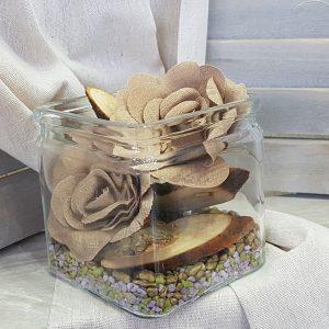 τετράγωνη γυάλα με χαλίκια, κορμούς και τεχνητά λουλούδια