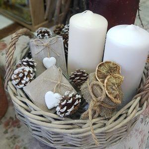 ψάθινο καλάθι με κηροπήγια, λευκά κεριά και κουκουνάρια