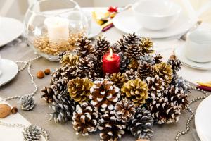 Στολισμός χριστουγεννιάτικου τραπεζιού με κουκουνάρια